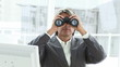 Mature businessman looking through binoculars