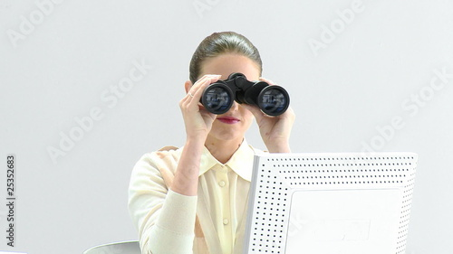 Elegant businesswoman looking through binoculars