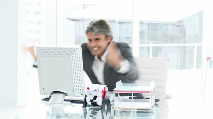 Successful mature businessman kissing his computer