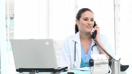attractive female doctor on phone in her office