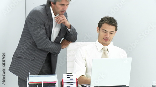 manager helping his assistant with computer