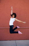 Beautiful young brunette girl jumping for joy