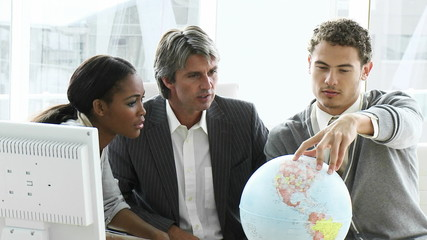 manager with two young executives looking at a terrestrial globe