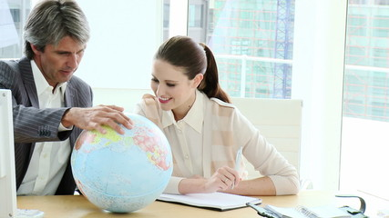 manager with young executive looking at a terrestrial globe