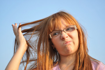 Girl with discontent looks at his hair