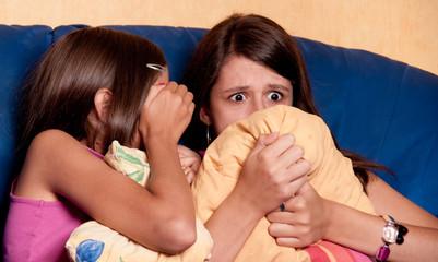 deux soeurs effrayées devant un film d'horreur