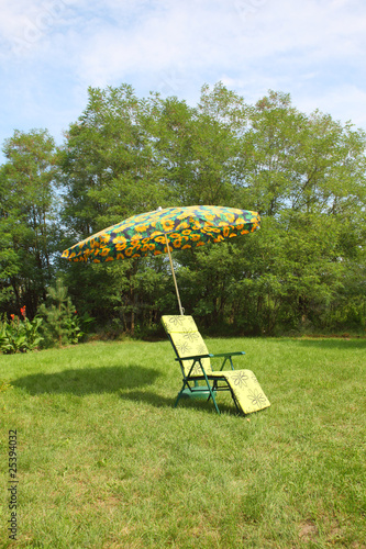Deck chair with umbrella on the grass