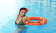 Young woman in a swimming pool with  a lifebuoy