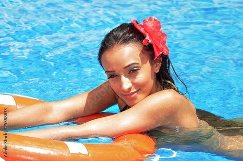 Young woman swimming in a  pool with  a lifebuoy