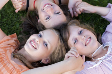 Cheerful friends girls laying in grass together. Selective focus