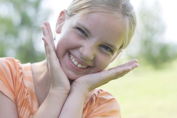 Isolated portrait shot of a cheerful girl holding her face in as