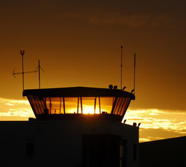 Air traffic control tower on sunset sky