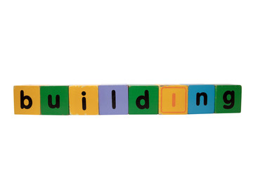 building in wood play block letters against white