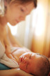 Mother with sleeping newborn baby daughter indoor