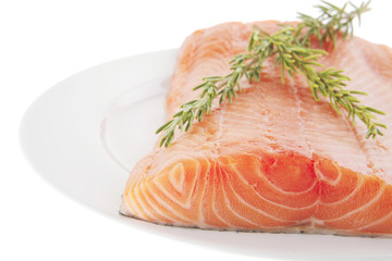 fresh uncooked salmon fillet on plate with rosemary