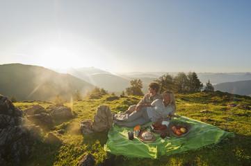 Junges Paar liegt auf einer Decke, die Aussicht genießen