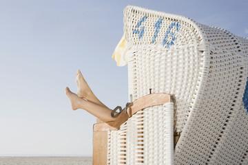 Deutschland, Schleswig Holstein, Amrum, Person entspannen im Strandkorb,