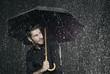 Mann im Regen mit Regenschirm