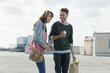 Deutschland, Berlin, Junges Paar stehen auf Parkebene lachen, Mann halten einen Apfel, Portrait