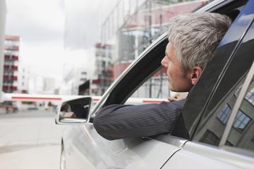 Deutschland, Hamburg, Geschäftsmann sitzen im Auto vor der geschlossenen Schranke