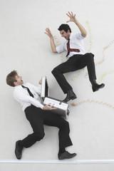 Zwei Geschäftsleute, einer springt aus dem Koffer des anderen