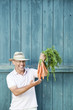 germany, bavaria, man in front of barn door holding bunch of carrots, smiling, portrait