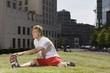 Deutschland, Berlin, Stretching Junger Mann auf dem Rasen