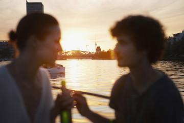 Deutschland, Berlin, Junges Paar auf dem Boot, mit Flaschen, Seitenansicht, Portrait