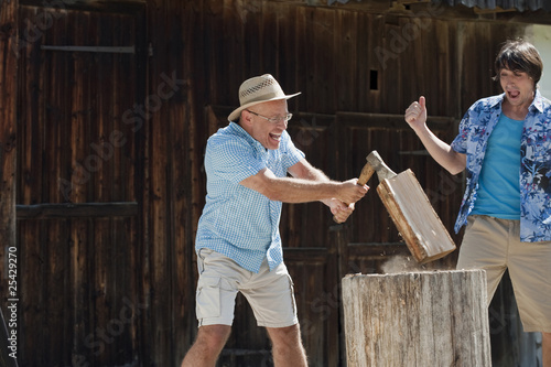 germany, bavaria, senior man chopping wood, man in background cheering