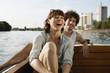 Deutschland, Berlin, Junges Paar auf dem Motorboot, lachen, Porträt