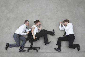 Drei Geschäftsleute, Geschäftsmann schiebt Geschäftsfrau im Bürostuhl
