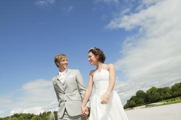 Deutschland, Bayern, Braut und Bräutigam spazieren gehen im Park, Hände halten, lächeln, Porträt