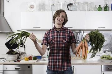 Deutschland, Junger Mann in der Küche mit Bund Karotten und Frühlingszwiebeln, lachen, Porträt
