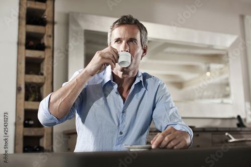 germany, hamburg, man sitting at table, drinking cup of espresso