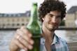 Deutschland, Berlin, Junger Mann halten eine Flasche, Portrait, close-up