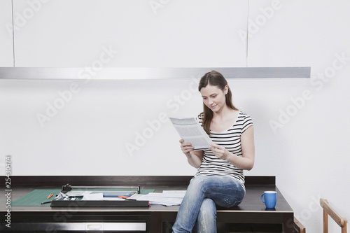 woman sitting on desk reading document.