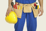 man wearing tool belt and holding hard hat, mid section, close-up