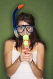 young woman wearing diving goggles, holding a water pistol