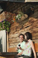 Italien, Südtirol, Paare vor Blockhaus halten Weingläser, Lächeln, Portrait