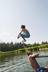 Italien, Südtirol, Vater und Sohn, Sohn springen in den See