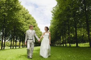 Deutschland, Bayern, Brautpaar im Park gehen Hände halten, lächeln, Porträt