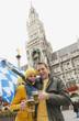 Deutschland, Bayern, München, Marienplatz, Couple halten Bierkrüge und bayerische Fahne, lachen, Porträt