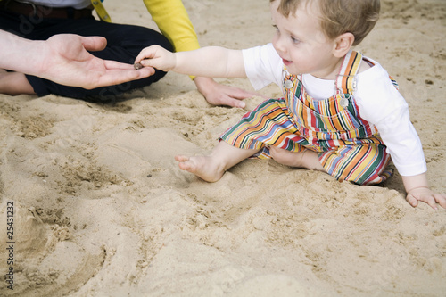 germany, berlin, family and son (2-3) in sandbox, side view, portrait
