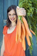Deutschland, Bayern, Frau halten Bündel von Karotten