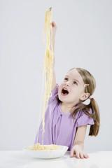 Mädchen spielen mit Spagetti