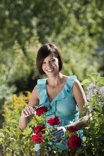 germany, bavaria, woman pruning flowers in garden