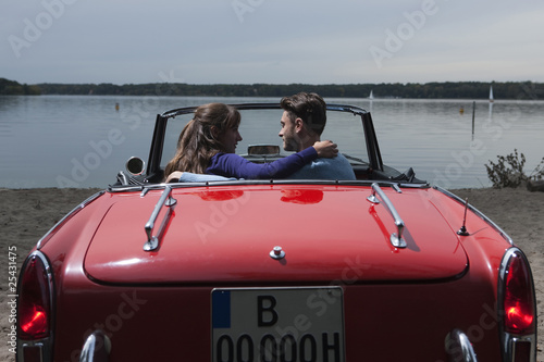 germany, berlin, lake wannsee, young couple in cabriolet embracing, side view, portrait