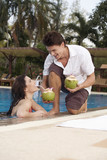 asia, thailand, man handing cocktail to woman in pool