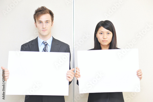 two business person holidng a white board