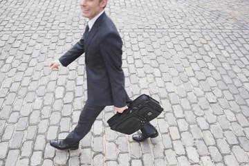 Deutschland, Hamburg, Geschäftsmann spazieren gehen in Straße mit Kopfsteinpflaster, Seitenansicht